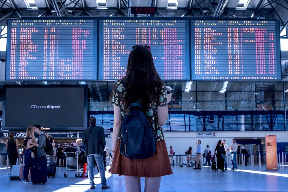 woman standing in the airport looking at flights