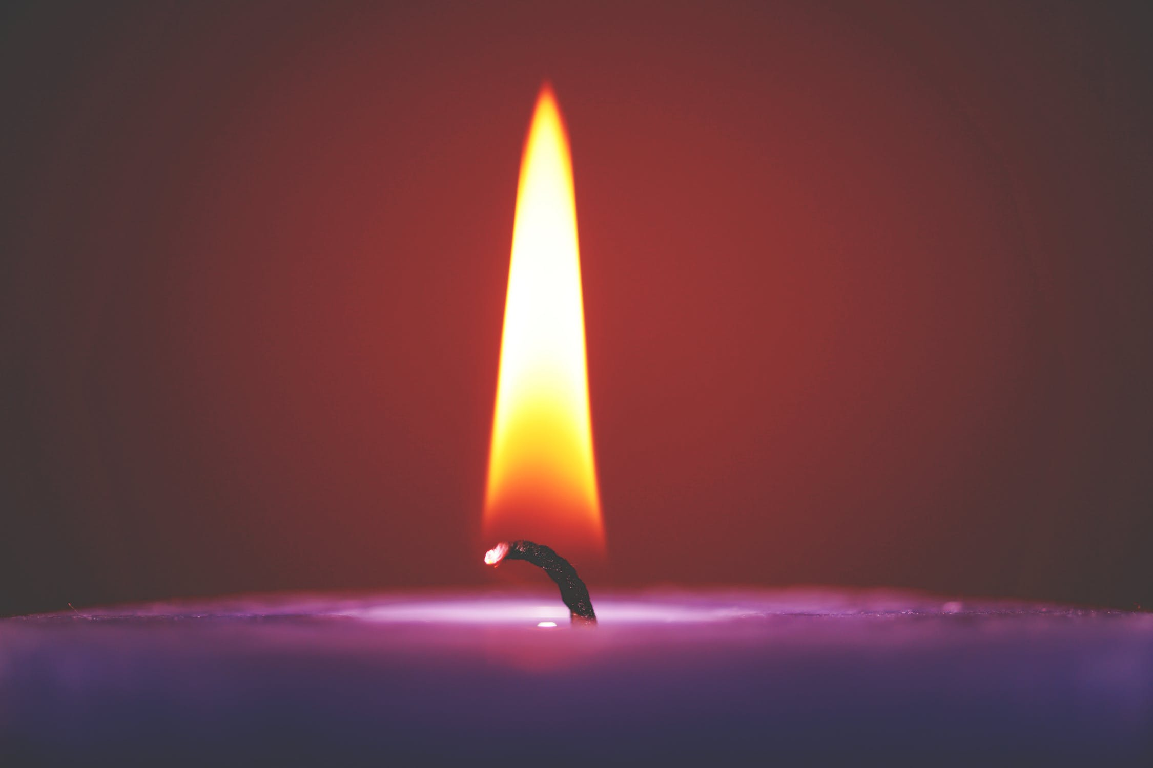 a purple-colored candle burning
