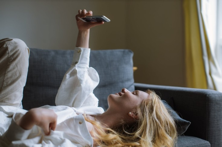 person at home covered in a blanket with a laptop and a glass of wine